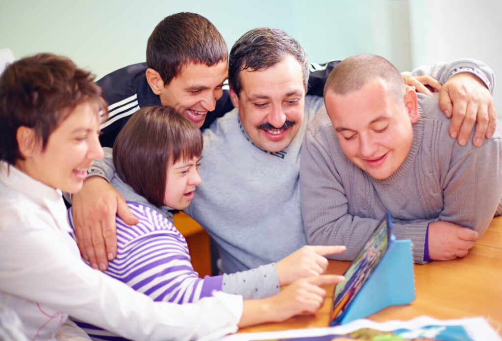 Supported Decision Making - group of happy people with disability having fun with tablet